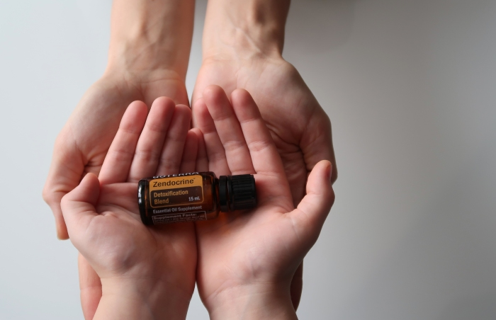 Mother's hands, child's hands, doTERRA zendocrine essential oil detoxification blend